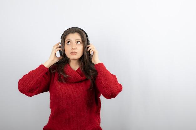 ヘッドフォンを身に着けている赤いセーターの若い女性の写真。