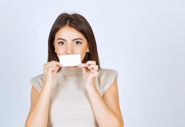 カードで口を覆ってポーズをとっている若い女性モデルの写真。