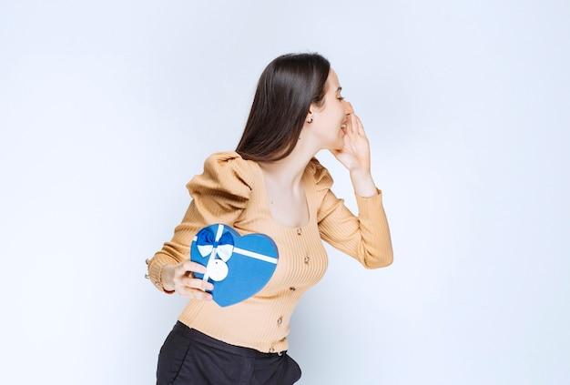 Фотография модели молодой женщины, держащей подарочную коробку в форме сердца против белой стены.