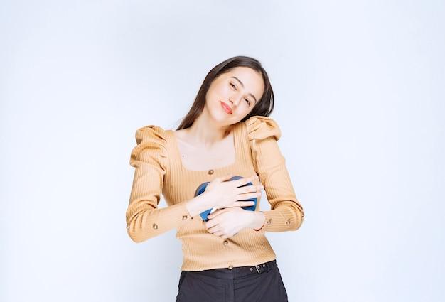 白い壁にハート型のギフトボックスを抱き締める若い女性モデルの写真。