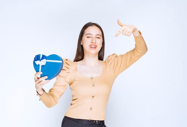 Фотография модели молодой женщины указывая на подарочную коробку в форме сердца против белой стены.