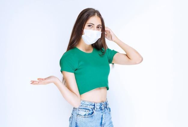 Фото молодой женщины модели стоя и носить защитную медицинскую маску.