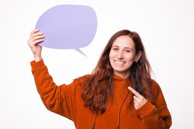 Фотография молодой женщины, указывающей на речевой пузырь из ее руки, смотрящей и улыбающейся в камеру