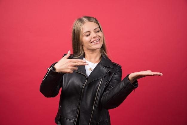 Фотография молодой женщины, стоящей и показывающей copyspace