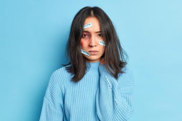 残酷な人に負傷した血まみれの目と打撲傷を負った虐待を受けた女性の写真は、犯罪虐待と戦うカジュアルなセーターを着ています