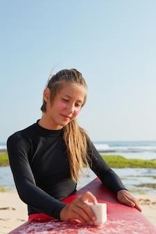 잠수복을 입은 활동적인 젊은 웨이크 서퍼의 사진, 조랑말 꼬리, 왁스 사용, 바위 해안선 근처에서 포즈, 비버 꼬리 착용