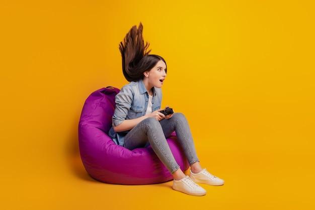 중독된 소녀의 사진은 비디오 게임을 하는 동안 조이스틱을 손에 들고 있습니다.