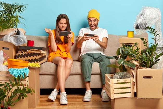 중독 된 밀레 니얼 세대의 남자와 여자의 사진은 스마트 폰에서 온라인 게임을합니다