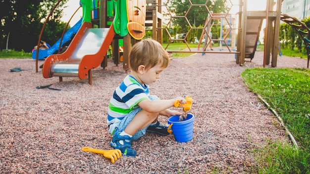 Фотография очаровательного 3-летнего мальчика, сидящего на детской площадке и копающего песок пластиковой лопаткой и ведром