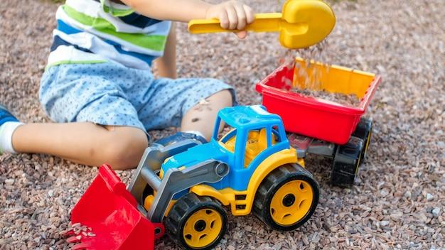 Фотография очаровательного 3-летнего мальчика, играющего с песком, и вашего грузовика с прицепом в парке. ребенок копает и строит в песочнице