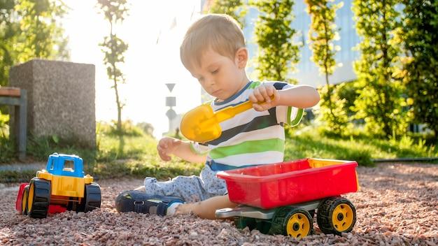 공원에서 모래와 트럭과 트레일러를 가지고 노는 사랑스러운 3살짜리 소년의 사진. 모래 구덩이에서 파고 건물을 짓는 어린이