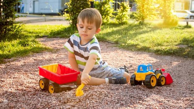모래를 가지고 노는 사랑스러운 3 세 유아 소년의 사진과 공원에서 트럭과 트레일러