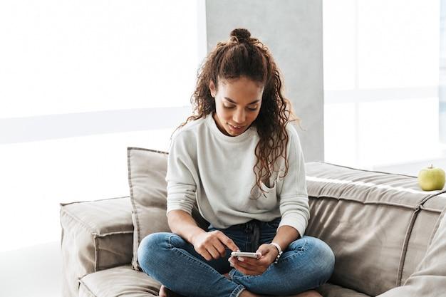 明るいアパートのソファに座っている間、携帯電話を使用して愛らしいアフリカ系アメリカ人の女性の写真