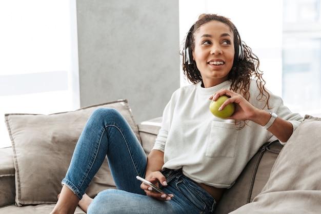 明るいアパートのソファに座って、携帯電話を使用してヘッドフォンを身に着けている愛らしいアフリカ系アメリカ人の女性の写真