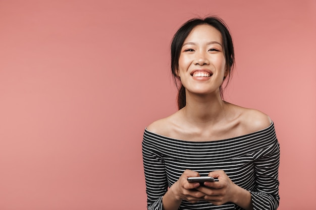 기본 복장을 한 사랑스러운 아시아 여성이 빨간 벽에 격리된 스마트폰을 들고 웃고 있는 사진