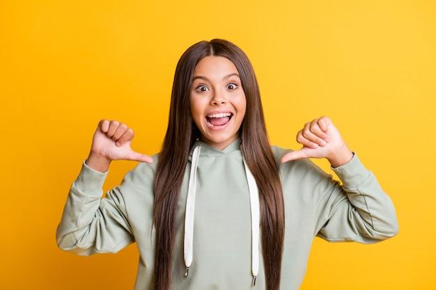 Фотография очаровательной красивой детской девочки, одетой в повседневный зеленый наряд, указывая на себя, показывает палец вверх, две руки, руки, изолированные на желтом цветном фоне