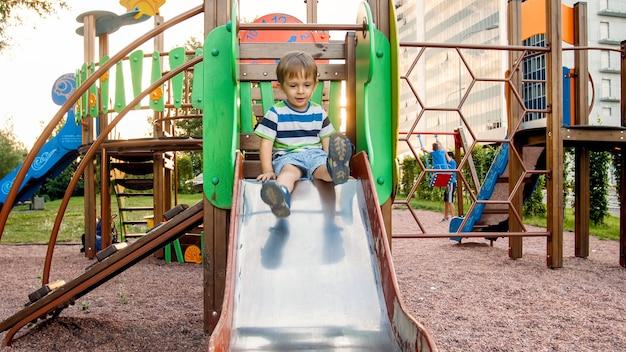 미끄럼틀을 타고 등반하는 사랑스러운 웃는 소년의 사진. 공원에서 즐겁게 노는 활동적인 아이
