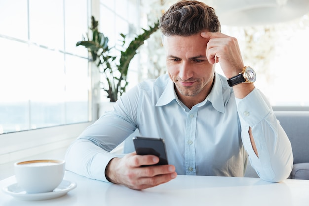 Фотография взрослого уверенного мужчины 30-х годов, сидящего в одиночестве в городском кафе с чашкой капучино и использующего черный смартфон