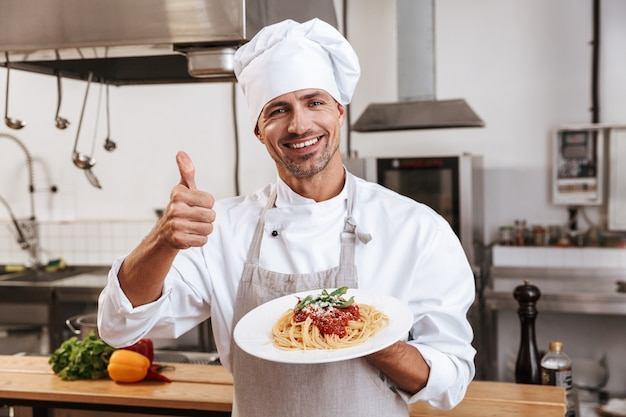 Фотография взрослого вождя мужского пола в белой форме, держащего тарелку с едой