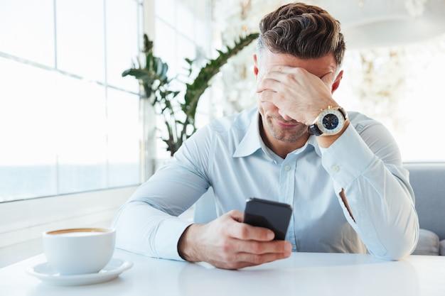 Фотография взрослого расстроенного мужчины 30-х годов, сидящего в одиночестве в городском кафе с чашкой капучино и подпирающего голову рукой при использовании черного смартфона