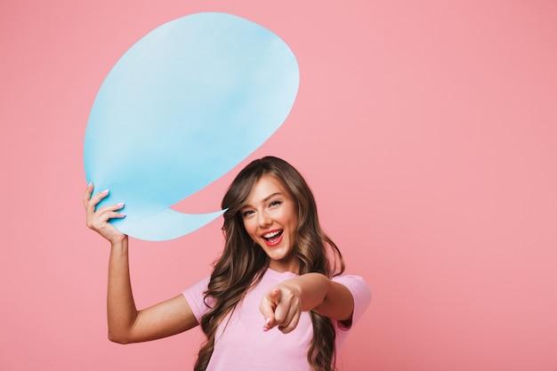 Фотография рекламной девушки 20-х годов в повседневной одежде, держащей над головой пустой плакат для текста copyspace и указывающей на вас пальцем с улыбкой, изолирована на розовом фоне