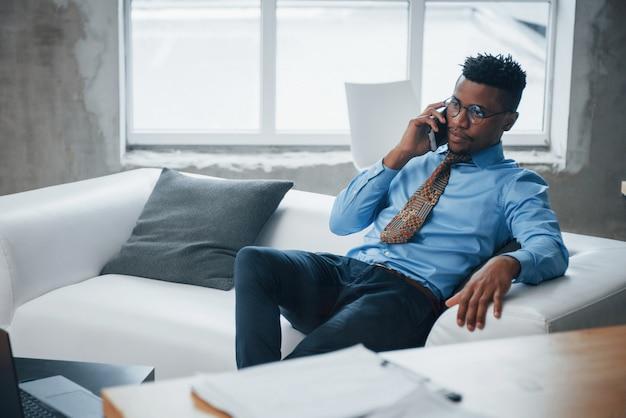 Фотография афро-американского молодого парня, сидящего на диване и разговаривающего по телефону