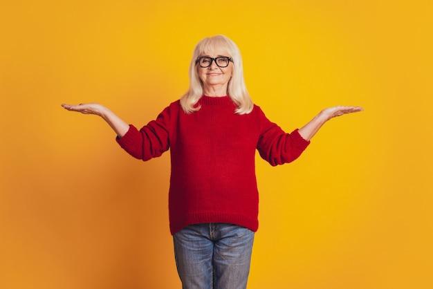 Фотография пожилой милой дамы с открытыми ладонями, предлагающая варианты копирования пространство желтый студийный фон