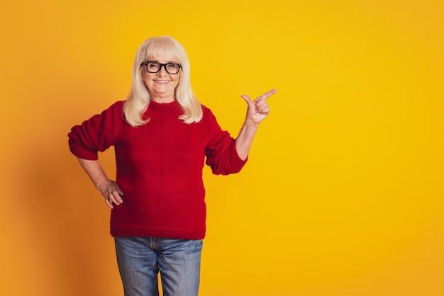 복사 공간 노란색 스튜디오 배경에 손가락을 옆으로 가리키는 나이 든 좋은 여자의 사진