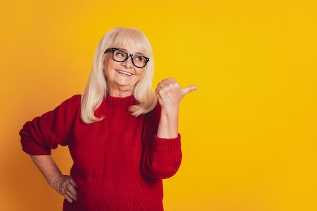 Фотография пожилой милой дамы, указывающей пальцами в сторону на желтом студийном фоне