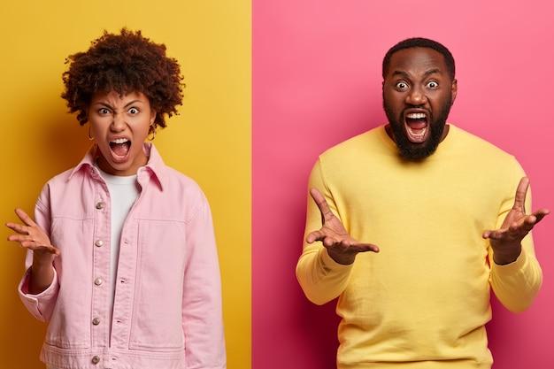 攻撃的な狂った民族のアフロの女性と男性のジェスチャーの写真は怒って