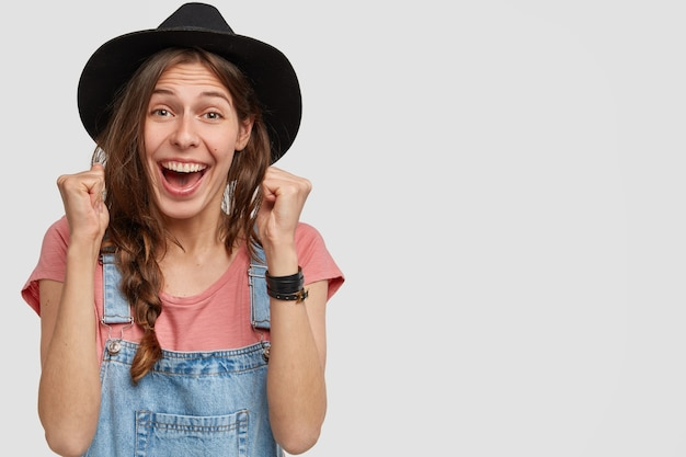 Фотография сельскохозяйственного работника в стильной шляпе, повседневной футболке и комбинезоне, торжествующе сжимающего кулаки, наконец, достигшего идеального результата, пораженного победой, изолированного над белой стеной, свободного пространства