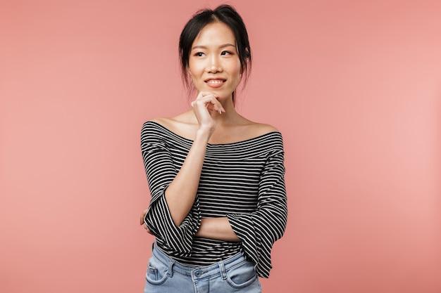 기본 옷을 입은 매혹적인 아시아 여성이 붉은 벽에 격리된 카피스페이스를 바라보며 웃고 있는 사진
