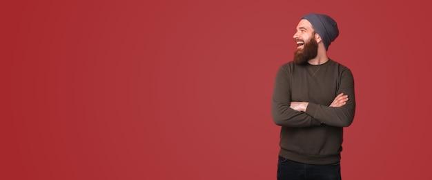 Фотография изумленного бородатого хипстера со скрещенными руками и смотрящего в сторону