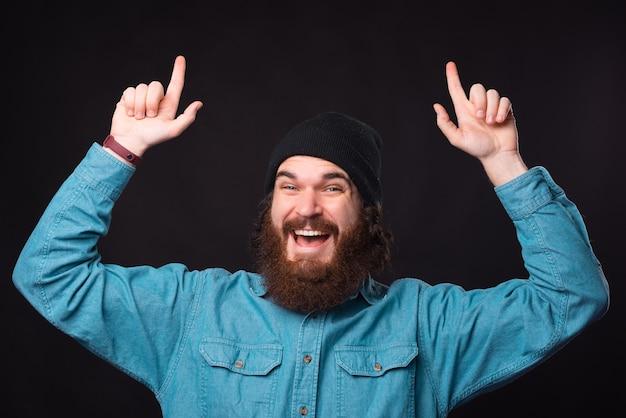 黒の背景の上に上向きの青いシャツを着た驚いたひげを生やした男の写真