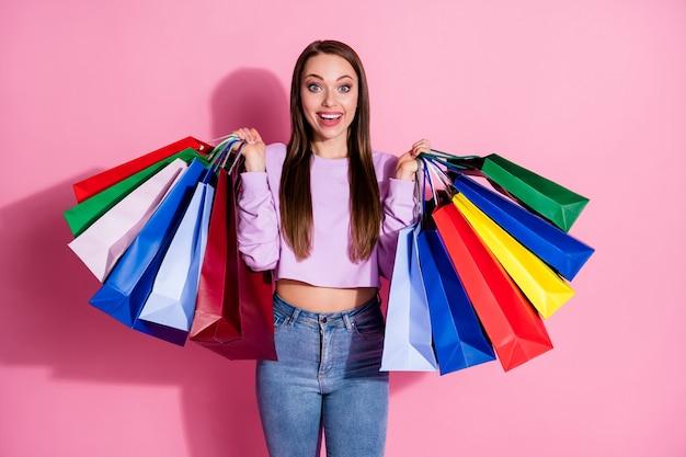 驚いた女の子の写真印象的なショッピング割引は、パステルカラーの背景の上に分離されたライラックスタイルのスタイリッシュなトレンディなセーターデニムジーンズを着用する多くのバッグを保持します