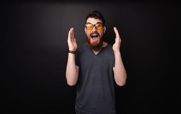 수염과 세련된 선글라스를 가진 놀란 남자의 사진, 어두운 배경 위에 와우 표현