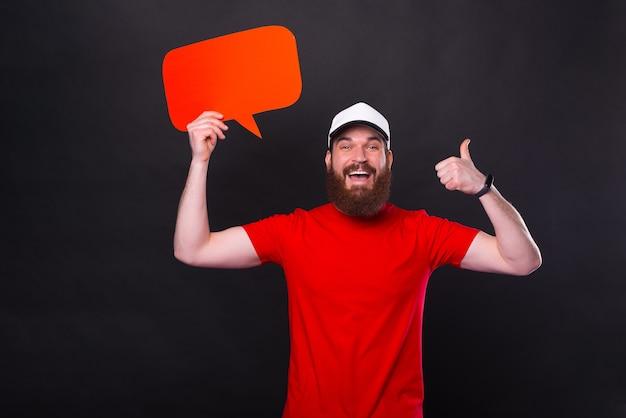Фотография изумленного мужчины с бородой в красной футболке, показывающего большой палец вверх и держащего пустой речевой пузырь copyspace