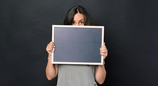 暗い背景の上に黒い空のチョークボードを保持し、顔を覆っている驚いた女性の写真