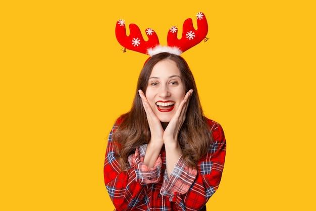 Фотография изумленной молодой женщины, празднующей рождество