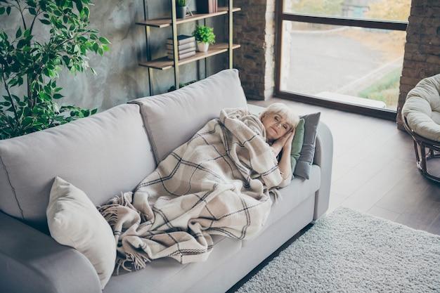 空想の横になっている快適なソファのソファのソファを持っている驚くべき金髪のおばあちゃんの写真は、格子縞の毛布を覆いました夢のようなかわいいは、屋内のリビングルームの頭の下で手を握ります