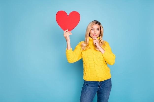 日付の招待状の正しい答えを考えている大きな赤い紙の心を保持している驚くべきブロンドの女性の写真は、ニットの黄色のプルオーバージーンズの孤立した青い色の壁を着用します