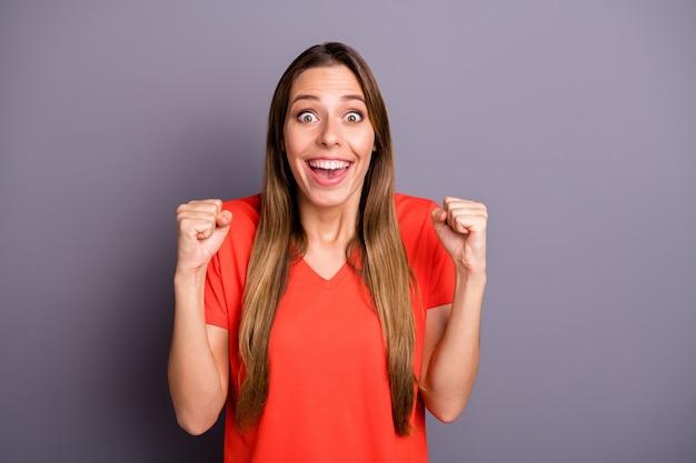 Фотография удивительной брюнетки в красной футболке, позирующей на фоне фиолетовой стены