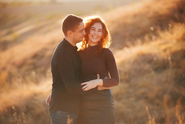 Фотография удивительной веселой пары, обнимающей на открытом воздухе в солнечном свете во время заката