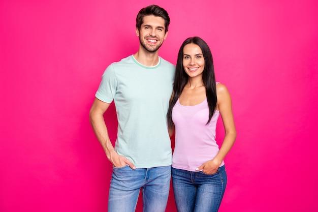 Фотография удивительной пары, парня и леди, стоящих и обнимающихся, наслаждаются лучшей повседневной одеждой компании, изолированной на ярко-розовом цветном фоне