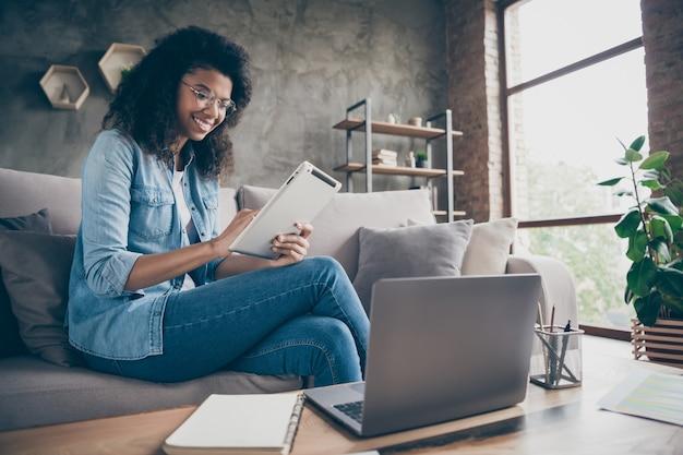 Фото удивительной темной кудрявой бизнес-леди, просматривающей планшет, ноутбук, стол, план записи, список, дневник, сидя, уютный диван, характеристики одежды, повседневная джинсовая одежда, квартира в помещении