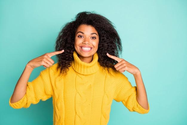 Фото удивительной темнокожей кудрявой дамы, указывающей пальцами на идеальное состояние зубов, реклама стоматолога в желтом вязаном пуловере, изолированная стена синего цвета