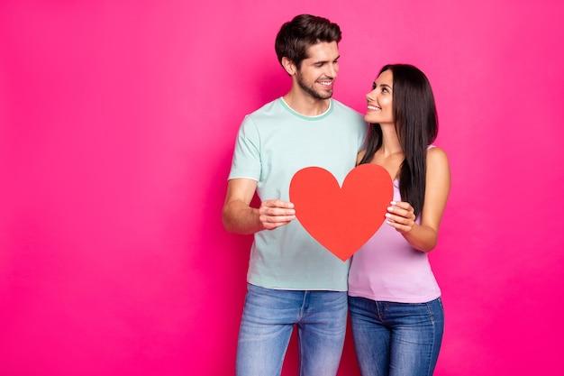최고의 감정을 표현하는 손에 큰 종이 마음을 잡고 포옹하는 놀라운 남자와 여자의 사진은 캐주얼 복장 격리 된 분홍색 배경을 착용