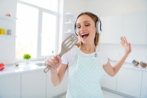 흰색 부엌 실내에 서명 마이크와 같은 혼합 숟가락을 들고 음악 현대 이어폰을 듣고 아침을 보내는 놀라운 주부의 사진 프리미엄 사진