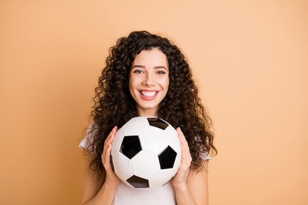 Фотография удивительной женщины, держащей большой белый черный кожаный футбольный мяч, взволнована, чтобы начать практиковать, носить белую повседневную одежду, изолированную бежевым пастельным цветом фона