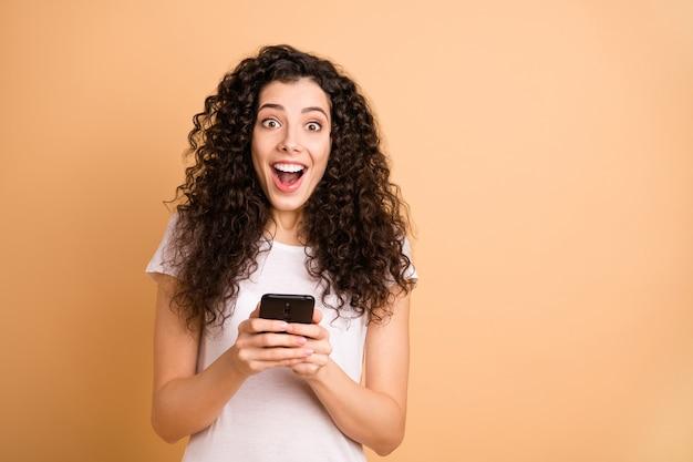 Фото удивительной женщины, держащей телефон за руки, зависимой от feednews, человек, проверяющий подписчиков, заметил, что новая белая повседневная одежда изолирована на бежевом фоне
